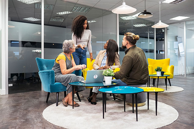 Group of coworkers meeting in an open urban office.