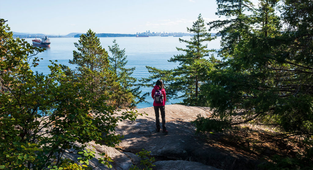Hiker close to cliff with forst in the background and overlooking a city in the distance.
