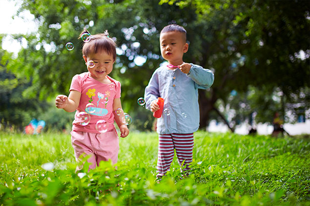 Young children playing in a field, blowing bubbles.
